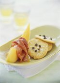 Honeydew melon with ham, with Parmesan and capers on cracker
