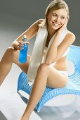 Young woman with towel round neck, sports drink in her hand