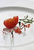 Miniature footballers training on plate of diced tomatoes
