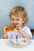 Small boy biting into a pretzel