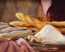 Still life with flour, yeast & baguettes (baked, unbaked)