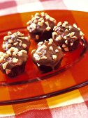 Snickers muffins with chopped peanuts on glass plate