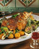 Easter roast lamb with artichokes and potatoes on a platter