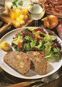 Cheese meatloaf with mixed salad leaves on plate