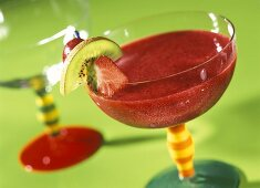 Strawberry and raspberry smoothie in glass with fruit kebab