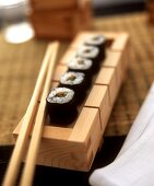 Hoso maki with fish and vegetables in wooden box with chopstick