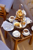 Cakes on tiered stand on small wooden table for afternoon tea