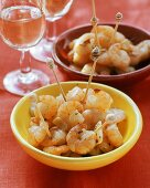 Garlic shrimps with cocktail sticks in bowls; white wine