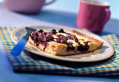 Piece of blueberry & almond cake with icing sugar