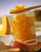 Apple and pumpkin preserve in jar and on wooden spoon