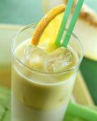 Honeydew melon drink with avocado, ice cubes & orange slice