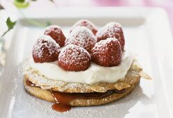 Strawberry almond tartlet with cream and icing sugar