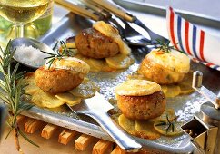 Rissoles with goat's cheese and potatoes on baking sheet