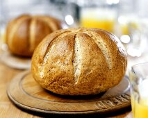 Round graham loaf on wooden plate