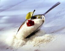 Preserving sugar with scoop and fresh cherry