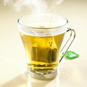 Steaming peppermint tea with tea bag in glass