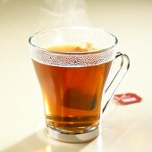 Hot red bush and vanilla tea with tea bag in glass