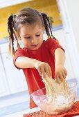 Small girl kneading pizza dough
