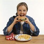 Model eating hamburger with chips