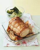 Roast pork roll with onions in glass dish