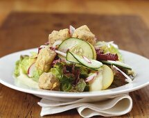 Salad leaves with pork cheeks, cucumber and radishes