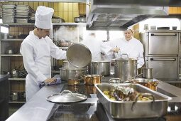 Chef examining the contents of a pan
