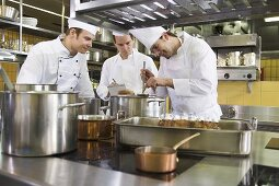 Chefs examining the contents of a soup ladle