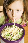 Girl eating ribbon pasta with ham & peas, without enthusiasm