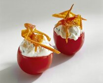 Two cherry tomatoes stuffed with soft cheese