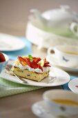 Piece of strawberry cake and cups of tea