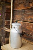 A close up of a milk can in front of wooden chalet