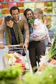 Family with full shopping trolley in a supermarket