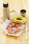 Bagel filled with ham and avocado spread