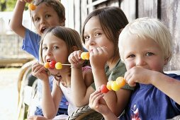 Four children eating melon skewers