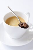 Spoonful of coffee beans on cup of coffee