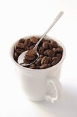 Coffee beans in cup with spoon