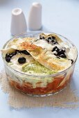 Lasagne with fish and olives in glass dish