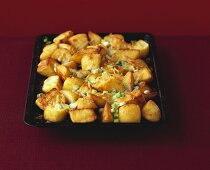 Roast potatoes with melted cheese and spring onions