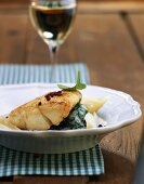 Fish fillet with pear slices on creamed spinach