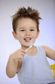 Small boy with yoghurt spoon in his hand