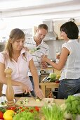 Kitchen scene: woman slicing vegetables, couple pouring wine