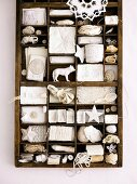 Type case filled with assorted white trinkets