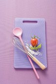 Chopping board, kitchen spoon, whisk, salt, rocket and tomato