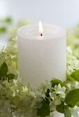 Candle in wreath of hydrangea flowers and mint