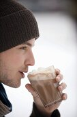Young man drinking cocoa with whipped cream
