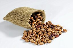 Pinto beans spilling out of hessian sack