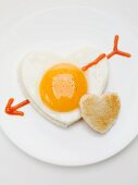 Heart-shaped fried egg with ketchup arrow and heart-shaped toast