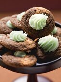 A bowl of chocolate macarooms with green cream