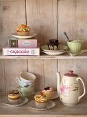 Cupcakes and tea things on wooden shelves