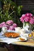 Apricot tart and peonies on garden table